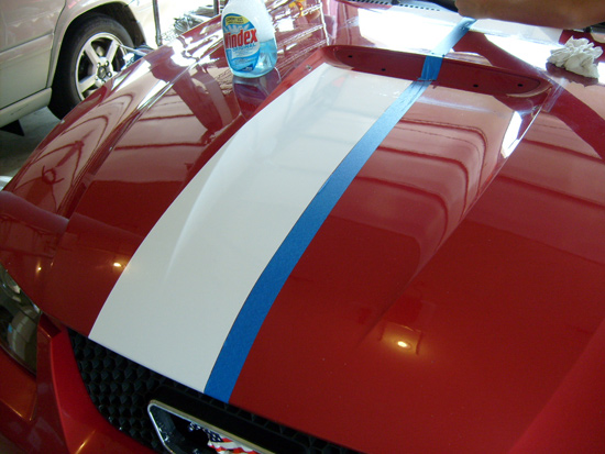 After the stripe is settled take a plastic scraper so as not to scratch the paint and scrape all of the windex out from under the stripe